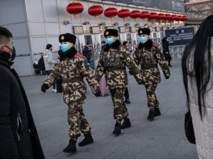 Chinese police officers wear protective masks as they patrol before the annual Spring Festival at a Beijing railway station on January 23, 2020 in Beijing, China. The number of cases of a deadly new coronavirus rose to over 500 in mainland China Wednesday as health officials locked down the city …