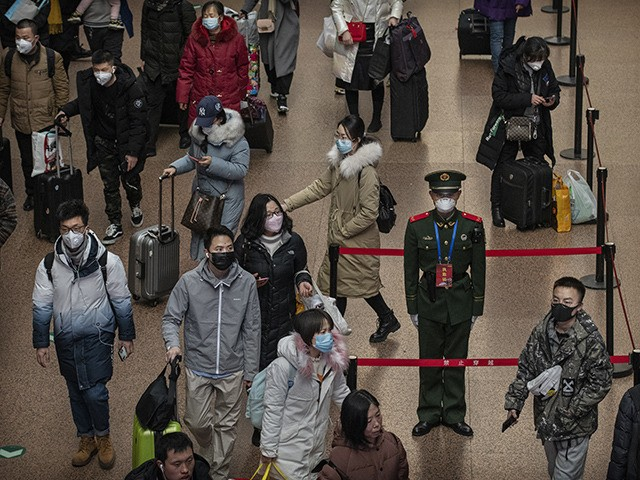 BEIJING, CHINA - JANUARY 23: A Chinese police officer wears a protective mask as passengers, many wearing masks also, arrive to board trains before the annual Spring Festival at a Beijing railway station on January 23, 2020 in Beijing, China. The number of cases of a deadly new coronavirus rose …