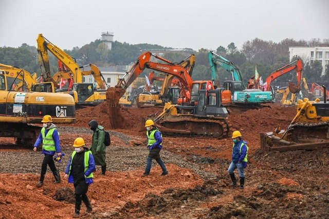 Employees work at a construction site of a hospital to treat patients during a virus outbreak in Wuhan in China's central Hubei province on January 24, 2020. - China is rushing to build a new hospital in a staggering 10 days to treat patients at the epicentre of a deadly virus outbreak that has stricken hundreds of people, state media reported on January 24. (Photo by STR / AFP) / China OUT (Photo by STR/AFP via Getty Images)