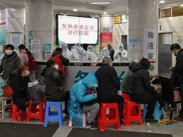 People wait as medical staff (back) wear protective clothing to help stop the spread of a deadly virus which began in the city, at Wuhan Red Cross Hospital in Wuhan on January 24, 2020. - Chinese authorities rapidly expanded a mammoth quarantine effort aimed at containing a deadly contagion on …