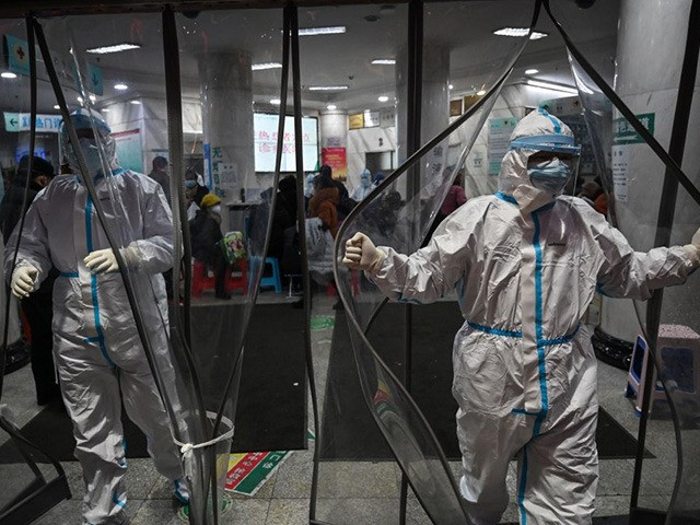 TOPSHOT - Medical staff members wearing protective clothing to help stop the spread of a deadly virus which began in the city, walk at the Wuhan Red Cross Hospital in Wuhan on January 25, 2020. - The Chinese army deployed medical specialists on January 25 to the epicentre of a …