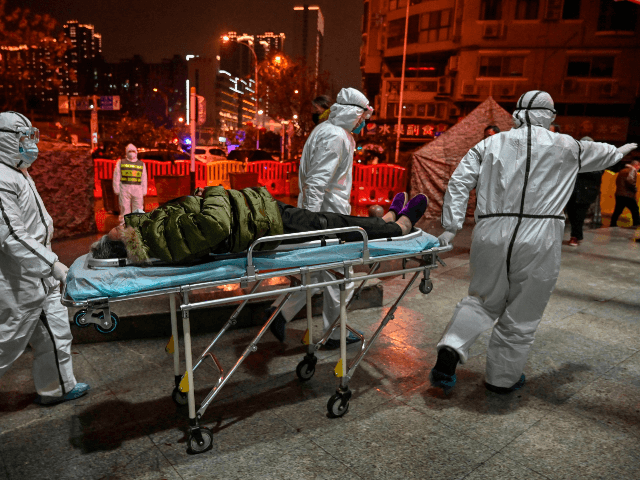 Medical staff members wearing protective clothing to help stop the spread of a deadly virus which began in the city, arrive with a patient at the Wuhan Red Cross Hospital in Wuhan on January 25, 2020. - The Chinese army deployed medical specialists on January 25 to the epicentre of …