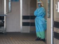 A member of the medical staff, wearing protective clothing to help stop the spread of a deadly SARS-like virus which originated in the central Chinese city of Wuhan, stands at an entrance to Princess Margaret Hospital in Hong Kong on January 26, 2020. - Hong Kong on January 25 classified …