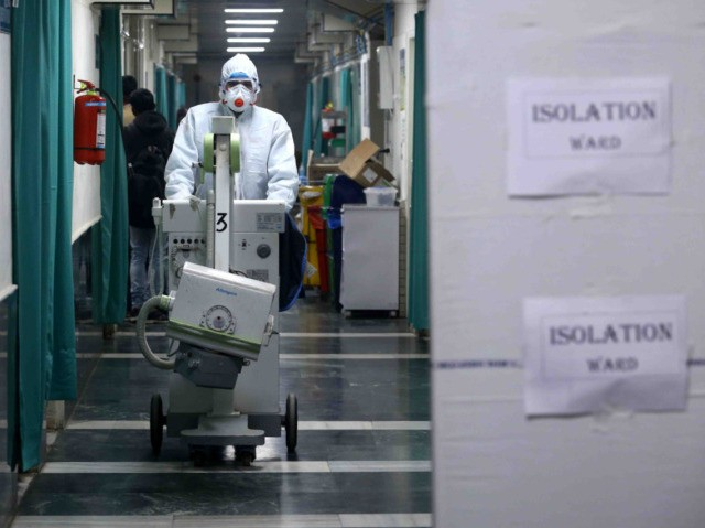 A medical staff member wearing protective clothing to help stop the spread of a deadly virus which began in Wuhan, works at an isolation ward in New Delhi on January 28, 2020, as 3 patients are under observation after returning from different part of China. - The epidemic, which experts …