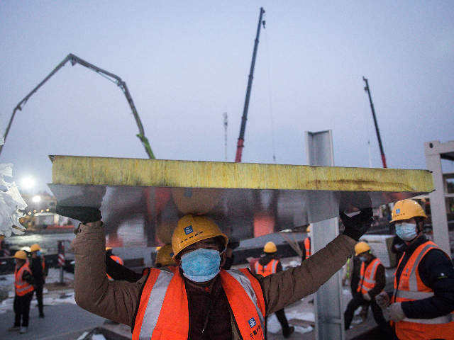 A worker carrying construction material at Huoshenshan hospital as new hospitals are built to tackle the coronavirus on January 28, 2020 in Wuhan, China. Wuhan Huoshenshan hospital will be completed on February 2nd and put into use on February 5th, with the capacity of 1000 beds. (Photo by Getty Images)