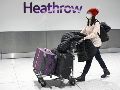 "Passengers wear face masks as the push their luggage after arriving from a flight at Terminal 5 of London Heathrow Airport in west London on January 28, 2020. - Chinese President Xi Jinping said Tuesday the country was waging a serious fight against the ""demon"" coronavirus outbreak and pledged transparency …"
