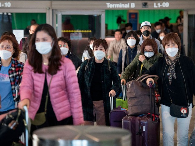 Passengers wear protective masks to protect against the spread of the Coronavirus as they arrive on a flight from Asia at the Los Angeles International Airport, California, on January 29, 2020. - A new virus that has killed more than one hundred people, infected thousands and has already reached the …