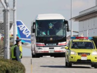A bus (C) carrying Japanese citizens departs following the arrival of the second charter flight from the Chinese city of Wuhan, which was arranged by Japan's government to evacuate its citizens, at Haneda airport in Tokyo on January 30, 2020. - Three Japanese evacuated from the epicentre of a deadly …