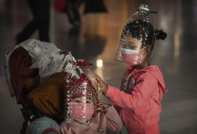 BEIJING, CHINA - JANUARY 30: Chinese children wear plastic bottles as makeshift homemade protection and protective masks while waiting to check in to a flight at Beijing Capital Airport on January 30, 2020 in Beijing, China. The number of cases of a deadly new coronavirus rose to over 7000 in …