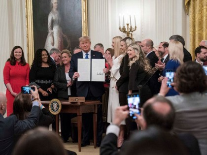 """WASHINGTON, DC - JANUARY 31: US President Donald Trump signs an executive order to create a new position for the Domestic Policy Council during the """"White House Summit on Human Trafficking: The 20th Anniversary of the Trafficking Victims Protection Act of 2000"""" event in the East Room of the White …"""