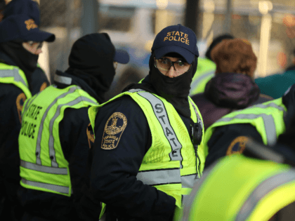 Virginia State Police stand watch over a security checkpoint as thousands of gun rights advocates attend a rally organized by The Virginia Citizens Defense League on Capitol Square near the state capital building January 20, 2020 in Richmond, Virginia. During elections last year, Virginia Governor Ralph Northam promised to enact …