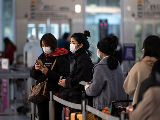 TOKYO, JAPAN - JANUARY 31: Passengers wearing masks wait at Spring Airlines' check-in counter to take a flight bound for Wuhan at Haneda airport on January 31, 2020 in Tokyo, Japan. The Chinese government arranged a charter flight operated by Spring Airlines for tourists from Wuhan to return to the …