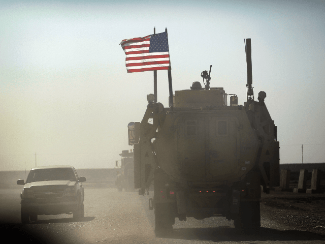 NASIRIYAH, IRAQ - DECEMBER 02: A U.S. Army armored vehicle flies an American flag as it provides security escort for a convoy of vehicles pulling equipment that is heading to Kuwait from Camp Adder as the Army continues to send it's soldiers and equipment home and the base is prepared …
