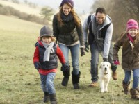 Family and dog having fun in the country in winter.