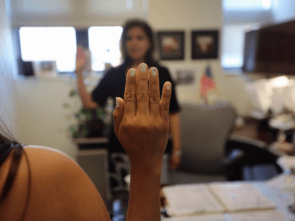 Colombian immigrant Paola Parra swears to tell the truth before taking her oral citizenship test at the U.S. Citizenship and Immigration Services (USCIS) Queens office on May 30, 2013 in the Long Island City neighborhood of the Queens borough of New York City. The branch office is located in an …