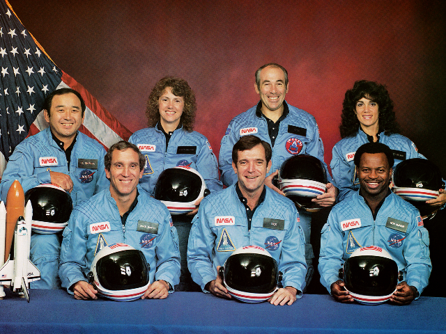 Space Shuttle Challenger crew members gather for an official portrait November 11, 1985 in an unspecified location. (Back, L-R) Mission Specialist Ellison S. Onizuka, Teacher-in-Space participant Sharon Christa McAuliffe, Payload Specialist Greg Jarvis and mission specialist Judy Resnick. (Front, L-R) Pilot Mike Smith, commander Dick Scobee and mission specialist Ron …