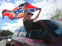 ROSEBURG, OR - OCTOBER 09: Chance White holds a confederate flag as he drives past protesters lining the street in front of the Roseburg Regional Airport on October 9, 2015 in Roseburg, Oregon. Most people turned out to protest President Obama's visit to Roseburg, as the community recovers from last …