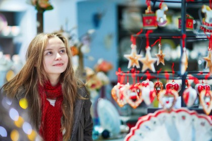 Girl at Christmas market looking at shop windows decorated for Christmas.