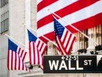 Wall Street Sign with New York Stock Exchange Building Out Of Focus In The Background