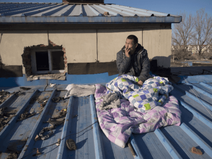 n this picture taken on December 11, 2017, a migrant worker who was evicted from his room in a low-income housing area sits on the roof of a house where he has been staying, as he waits to receive his salary before returning to his home in the south of …