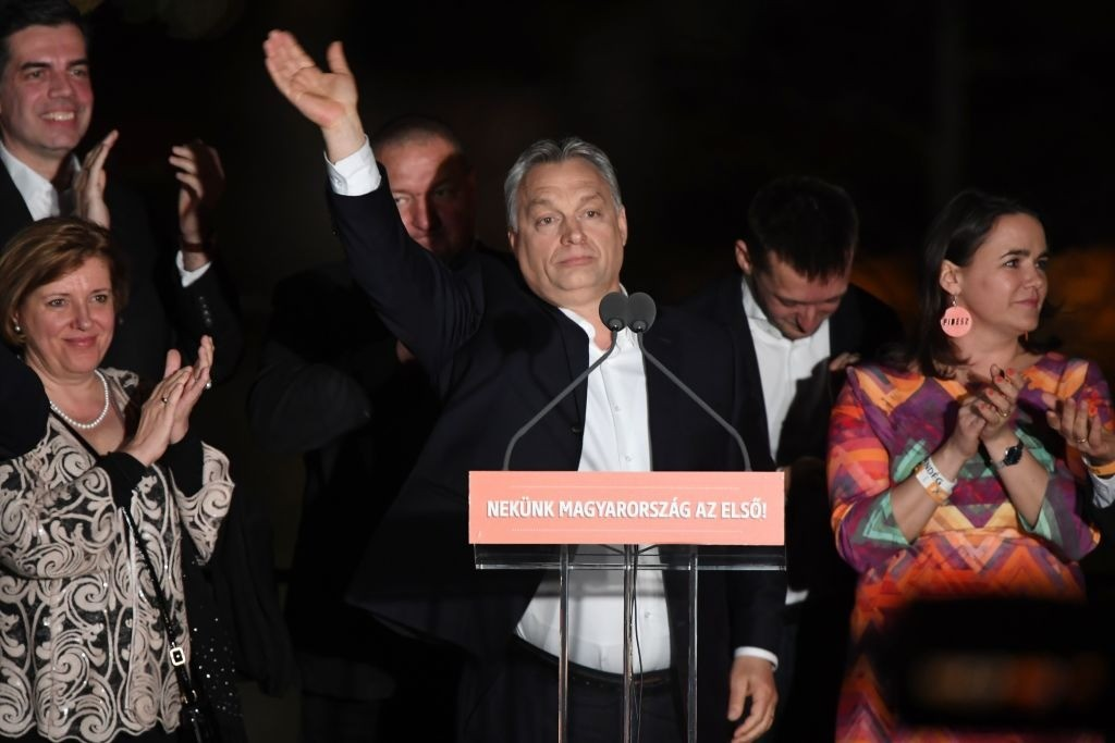 Hungarian Prime Minister Viktor Orban (C) and members of his FIDESZ party celebrate from the podium on the bank of the Danube River after winning the parliamentary election on April 8, 2018 in Budapest. The words on the lectern read 'Hungary is first for us!' / AFP PHOTO / ATTILA KISBENEDEK (Photo credit should read ATTILA KISBENEDEK/AFP via Getty Images)