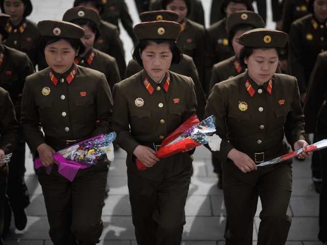 Female Korean People's Army (KPA) soldiers arrive to pay their respects before the statues of late North Korean leaders Kim Il Sung and Kim Jong Il, at Mansu hill in Pyongyang April 15, 2018. - Thousands of North Korean devotees laid flowers before statues of the country's founder Kim Il …