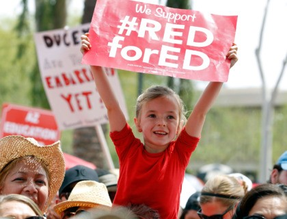 PHOENIX, AZ - APRIL 26: A young student holds up a sign in support of Arizona teachers during a #REDforED rally in front of the State Capitol on April 26, 2018 in Phoenix, Arizona. Teachers state-wide staged a walkout strike on Thursday in support of better wages and state funding …