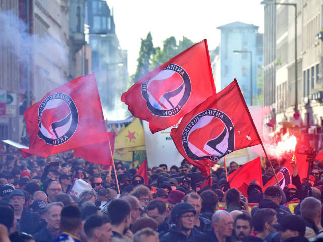 "Participants of the ""Revolutionary 1st of May Demonstration"" light flares and wave flags of the left-wing, Anti-Fascist Antifa movement during May Day events on May 1, 2018 in Berlin. (Photo by John MACDOUGALL / AFP) (Photo credit should read JOHN MACDOUGALL/AFP via Getty Images)"