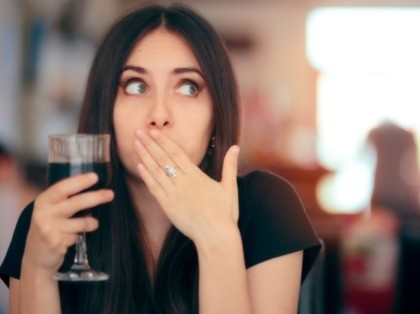 Woman covering her mouth after drinking wine