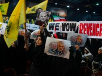 "Supporters of Hezbollah leader Sayyed Hassan Nasrallah wave flags and placards that say ""we vow revenge,"" ahead of the leader's televised speech in a southern suburb of Beirut, Lebanon, Sunday, Jan. 5, 2020 following the U.S. airstrike in Iraq that killed Iranian Revolutionary Guard Gen. Qassem Soleimani. The placard in …"