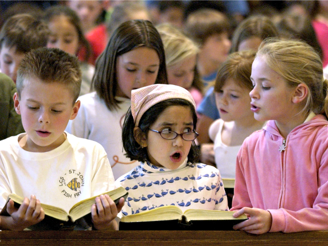 Lawrence Catholic School students Adam Wagner, 8, left, Isabel Cartter, 6, center, and Marlee Bird, 8, right, along with about 300 classmates sing songs during a prayer service for an ailing Pope John Paul II at St. John the Evangelist Church in Lawrence, Kan. Friday, April 1, 2005. (AP Photo/Charlie …
