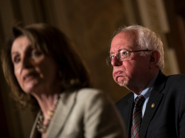 (L to R) House Minority Leader Nancy Pelosi (D-CA) speaks as Sen. Bernie Sanders (D-VT) looks on during a press conference to discuss legislation for a 15 dollar minimum wage, on Capitol Hill, May 25, 2017 in Washington, DC. 31 Democrats have pledged to support the legislation so far. (Photo …
