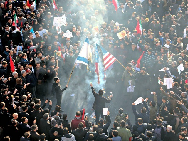Iranians set a US and an Israeli flag on fire during a funeral procession organised to mourn the slain military commander Qasem Soleimani, Iraqi paramilitary chief Abu Mahdi al-Muhandis and other victims of a US attack in the capital Tehran on January 6, 2020. - Mourners packed the streets of …