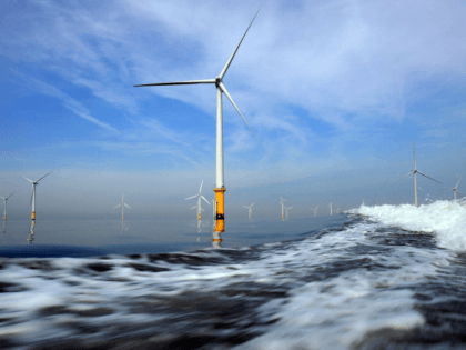 LIVERPOOL, UNITED KINGDOM - MAY 12: Turbines of the new Burbo Bank off shore wind farm lay in the wake of a maintenance boat in the mouth of the River Mersey on May 12, 2008 in Liverpool, England. The Burbo Bank Offshore Wind Farm comprises 25 wind turbines and is …