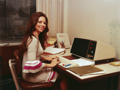 A woman in a knit dress with flared sleeves works at an early model desktop computer made by Servus, 1970s. (Photo by Hulton Archive/Getty Images)