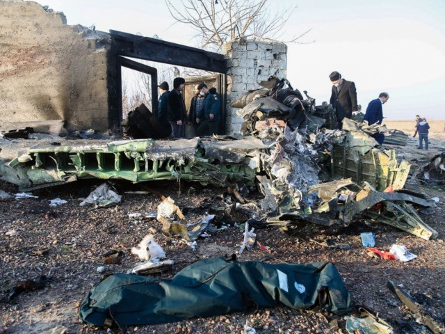 TOPSHOT - People stand near the wreckage after a Ukrainian plane carrying 176 passengers crashed near Imam Khomeini airport in Tehran on January 8, 2020. - All 176 people on board a Ukrainian passenger plane were killed when it crashed shortly after taking off from Tehran on January 8, Iranian …