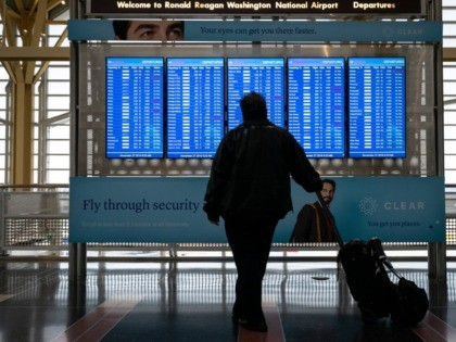 ARLINGTON, VA - NOVEMBER 27: A passenger looks at the departures board at Ronald Reagan National Airport on the day before the Thanksgiving holiday, November 27, 2019 in Arlington, Virginia. Both the American West and Midwest are facing significant weather events that could impact travelers. (Photo by Drew Angerer/Getty Images)