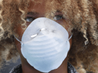 Levi Draheim, 11, wears a dust mask as he participates in a demonstration in Miami in July 2019. A lawsuit filed by him and other young people urging action against climate change was thrown out by a federal appeals court Friday. Wilfredo Lee/AP