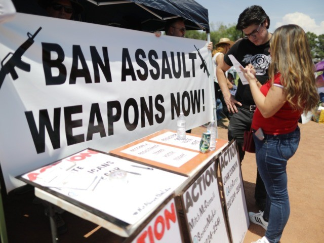 EL PASO, TEXAS - AUGUST 07: A 'Ban Assault Weapons Now' sign is displayed near a voter registration table at a protest against President Trump's visit, following a mass shooting which left at least 22 people dead, on August 7, 2019 in El Paso, Texas. Protestors also called for gun …
