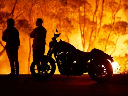 LAKE TABOURIE, AUSTRALIA - JANUARY 04: Residents look on as flames burn through bush on January 04, 2020 in Lake Tabourie, Australia. A state of emergency has been declared across NSW with dangerous fire conditions forecast for Saturday, as more than 140 bushfires continue to burn. There have been eight …
