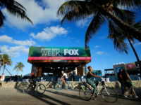 Cyclists ride past the FOX Sports South Beach studio compound prior to Super Bowl LIV on January 25, 2020 in Miami Beach, Florida. The San Francisco 49ers will face the Kansas City Chiefs in the 54th playing of the Super Bowl, Sunday February 2nd. (Photo by Cliff Hawkins/Getty Images)