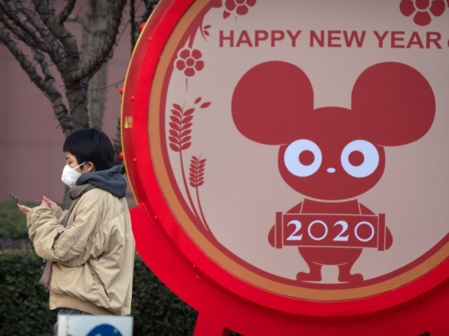 A woman wears a face mask standing near a display for the upcoming Lunar New Year, the Year of the Rat, in Beijing, Wednesday, Jan. 22, 2020. Chinese health authorities urged people in the city of Wuhan to avoid crowds and public gatherings, after warning on Wednesday that a new …