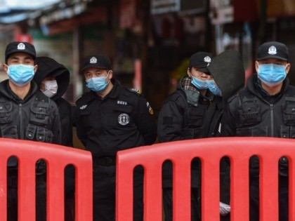 A police officers and security guards stand outside the Huanan Seafood Wholesale Market where the coronavirus was detected in Wuhan on January 24, 2020 - The death toll in China's viral outbreak has risen to 25, with the number of confirmed cases also leaping to 830, the national health commission …