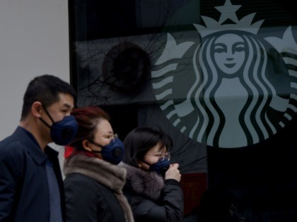 People wearing protective face masks walk past a closed Starbucks coffee shop at a grocery in Beijing on January 29, 2020. - People in Beijing and across China are donning masks, spraying antiseptic and staying off the streets in a battle to halt the spread of a viral outbreak that …