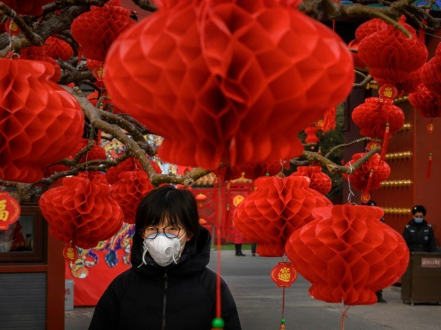 A Chinese woman wears a protective mask as she stands with decorations marking the Chinese New Year holiday at the site of a temple fair that was cancelled on January 26, 2020 in Beijing, China. The number of cases of a deadly new coronavirus rose to over 2000 in mainland …