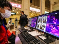 TOPSHOT - A staff member screens arriving passengers with thermal scanners at Hankou railway station in Wuhan, in China's central Hubei province on January 21, 2020. - Asian countries on January 21 ramped up measures to block the spread of a new virus as the death toll in China rose …