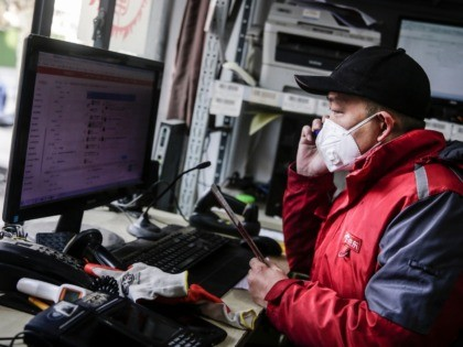 WUHAN, CHINA - JANUARY 29: (CHINA OUT) A courier checks orders on a computer in an Express station on January 29, 2020 in Hubei Province, Wuhan, China. Due to a transit shut down and lack of supplies, couriers have became the city's suppliers. The 2019 coronavirus (2019-nCoV), which originated in …