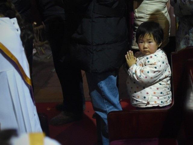 A young Chinese worshipper attends the Christmas Eve mass at a Catholic church in Beijing on December 25, 2014 as Christians around the world prepare to celebrate the holy day. / AFP / WANG ZHAO (Photo credit should read WANG ZHAO/AFP via Getty Images)