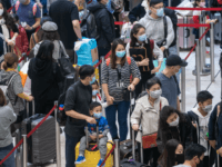 HONG KONG, CHINA - JANUARY 23: Travellers wearing face mask wait in line at the departure hall of West Kowloon Station on January 23, 2020 in Hong Kong, China. Hong Kong reported its first two cases of Wuhan coronavirus infections as the number of those who have died from the …
