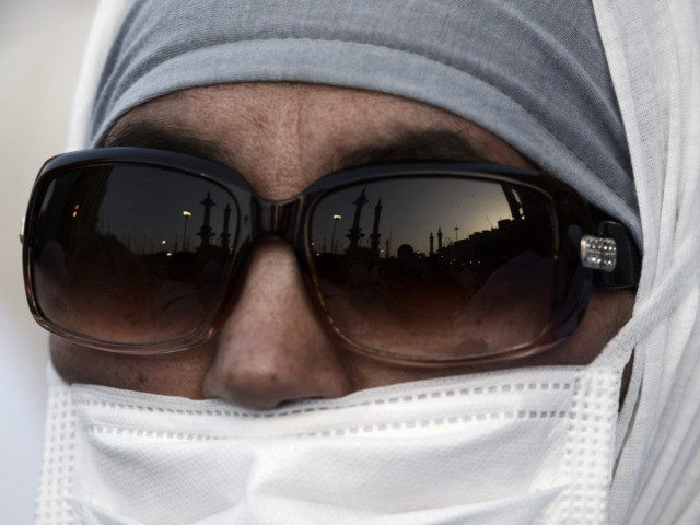 "A Muslim pilgrim wearing a mask arrives for a prayer at Mecca's Grand Mosque, home of the cube-shaped Kaaba or ""House of God"" that Muslims believe was built by Abraham 4,000 years ago, on September 29, 2014 as hundreds of thousands of Muslim worshipers started pouring into the holy city …"